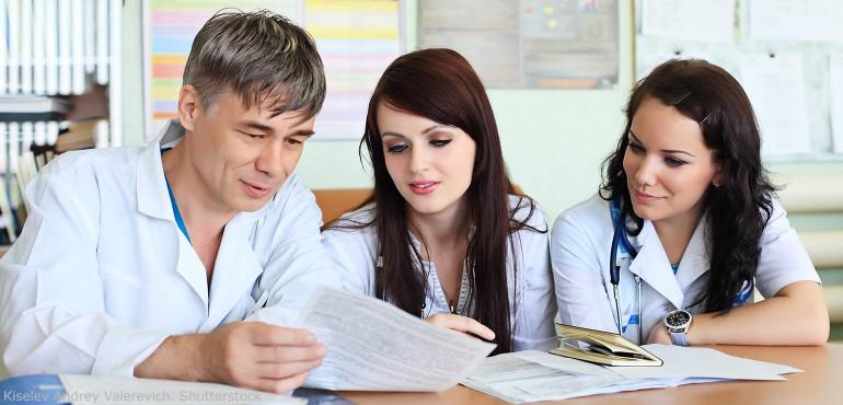 Male nurse talking with two female nurses