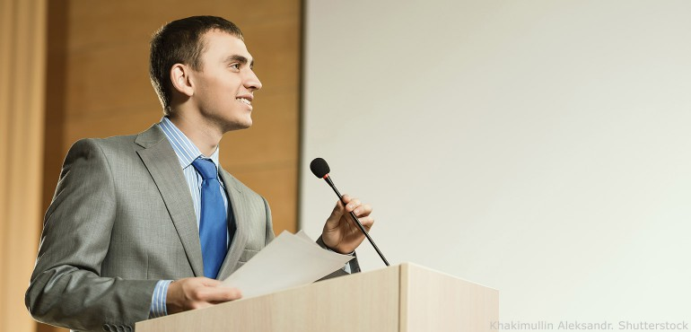 Male presenter standing at podium holding the microphone