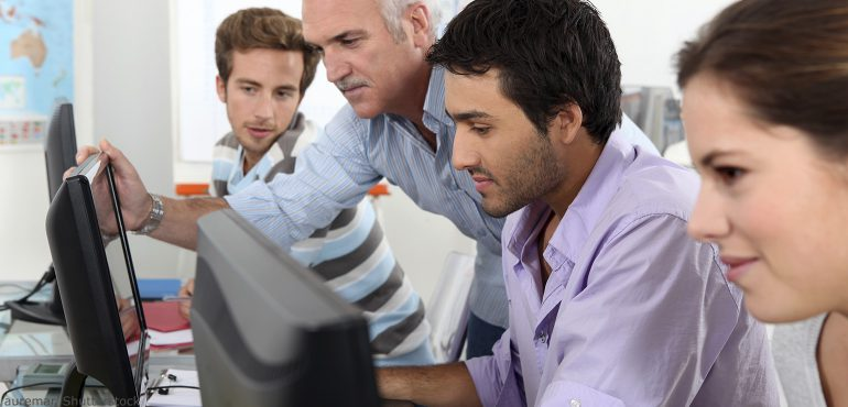 Male professor and three students sitting at computer terminals working