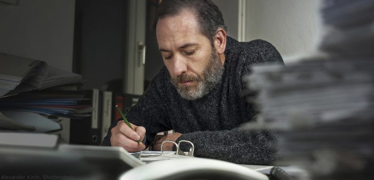 Male professor sitting in his office looking at a notebook
