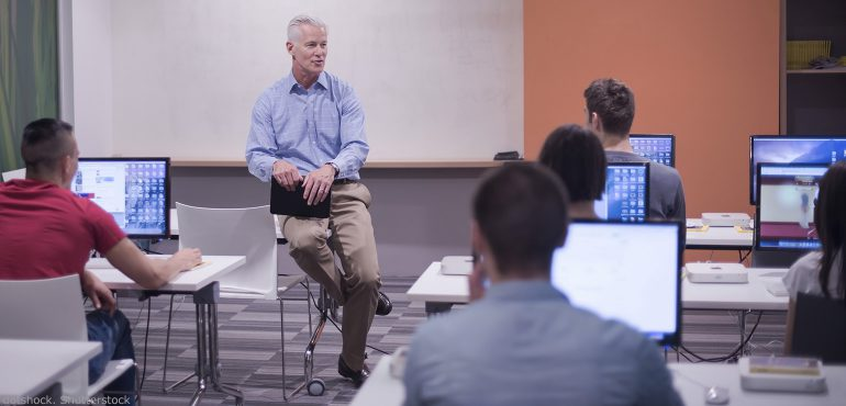 Male professor sitting on table while lecturing to a classroom of students