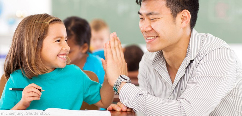 Male teacher giving a high five-to a female elementary school student