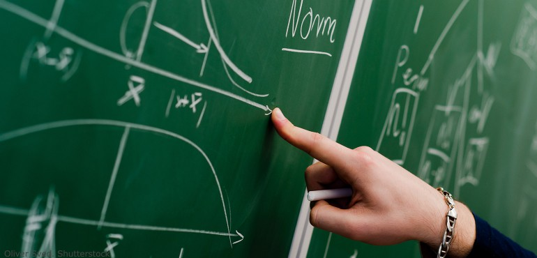 Math equations written on a green chalkboard with a finger pointing