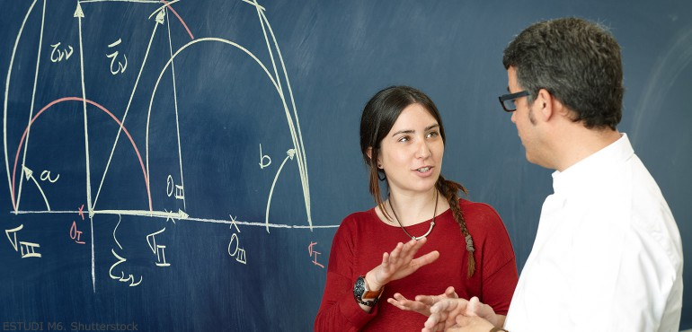 Math professor talking with female student next to a chalkboard