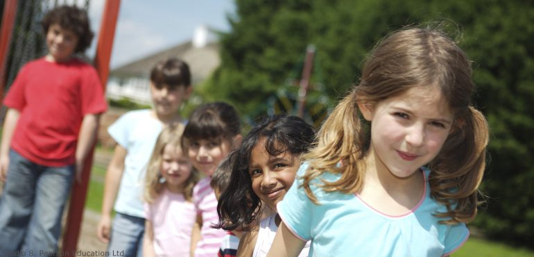 Multiracial children standing in a line outside in a playground