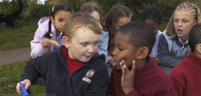 Multiracial elementary students sitting outside talking with each other