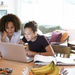 Mother helping tween daughter doing homework at laptop in kitchen
