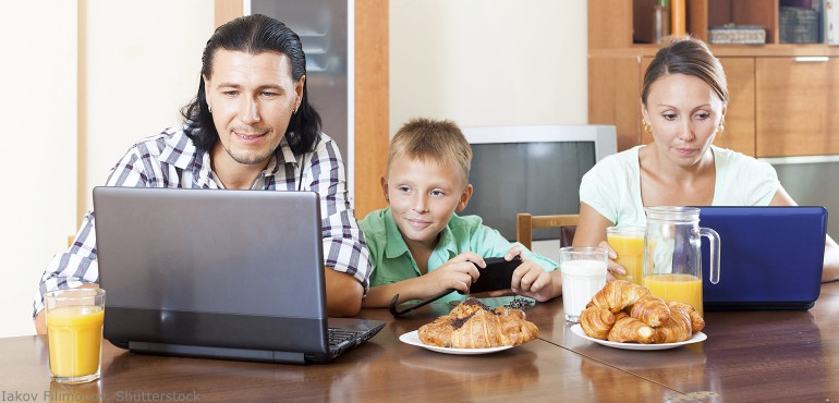 Parents and child sitting at table looking laptop computers