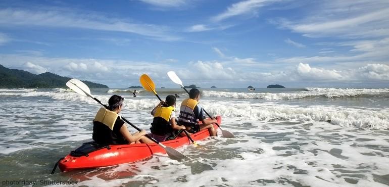People rowing paddle board in ocean
