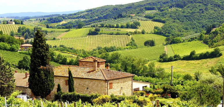 Rolling green hills and a villa in the Tuscan region of Italy