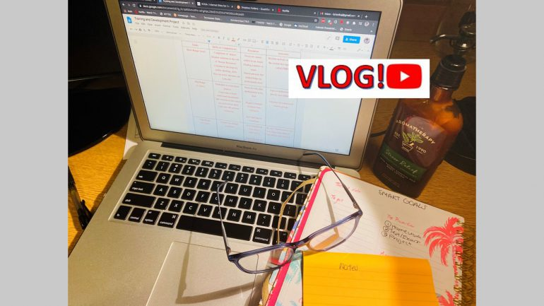 a laptop and student papers with the word 'vlog'