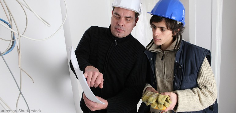 Senior electrician training a new one on the job