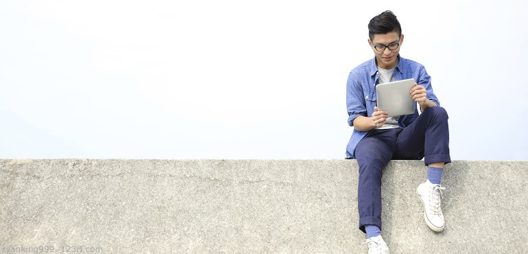 Smiling Asian male college student sitting on a wall looking at a digital tablet