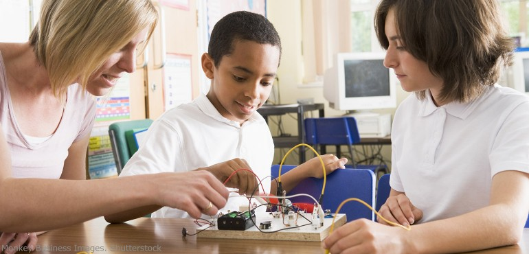 Teacher and two students building a radio