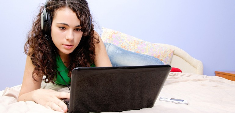 Teenage girl lying on bed using a laptop