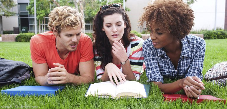 Three college students laying on the grass looking at an open textbook
