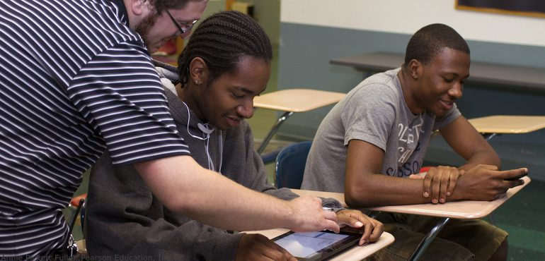 Three male multi racial students working with digital mobile devices in a classroom