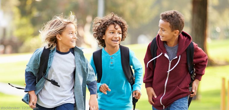 Three multiracial boys walking and talking together