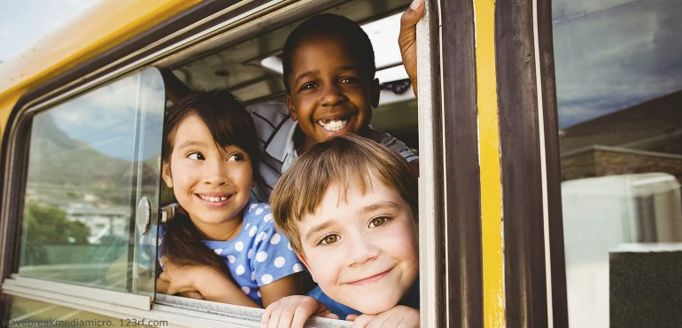 Three multiracial children looking out schoolbus window