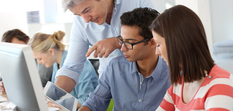 Three people working together around a computer and tablet