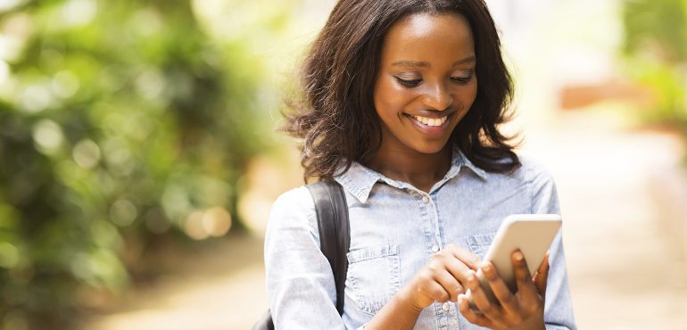happy young african american uni student using cell phone for online, social media