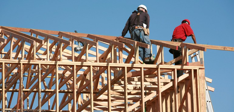 Two construction workers walking on the frame of a house