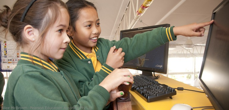 Two elementary school girls playing on a computer