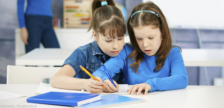 Two elementary school girls sitting together working on a problem in class