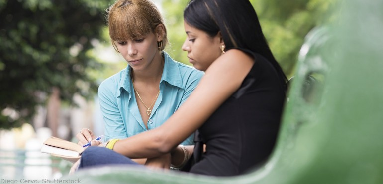 Two female college students sitting on a bench in a park and studying