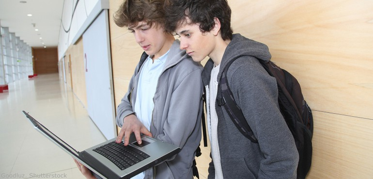 Two high school boys holding a laptop and looking at the screen