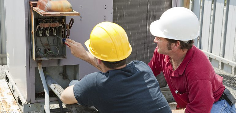 Two male electricians working on an air conditioning unit