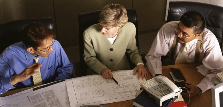 Two men and a woman working in a conference room looking at documents