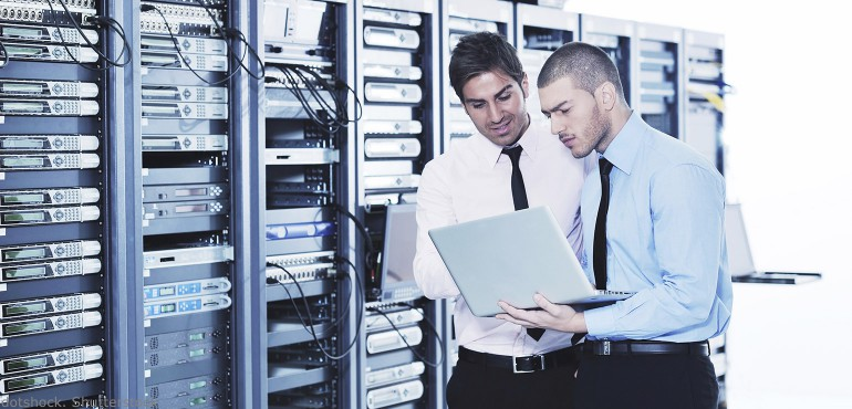 Two men standing in a room full of computer servers and looking at a laptop