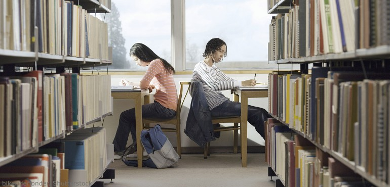 Two students studying in a library near rows of books