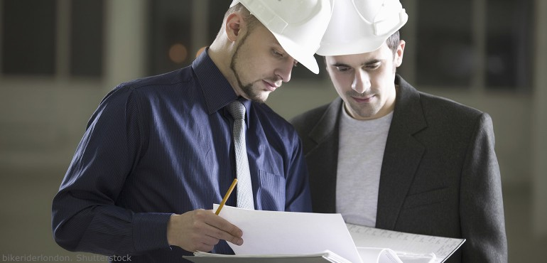 Two young men wearing white hard hats and looking at a binder