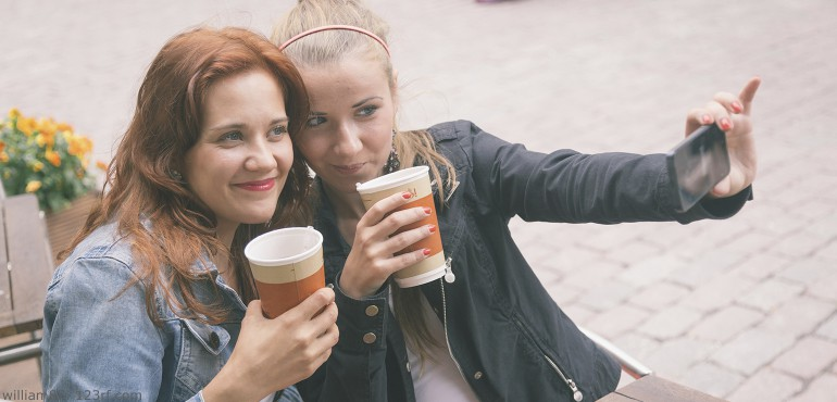 Two young women posing together and taking a selfie picture