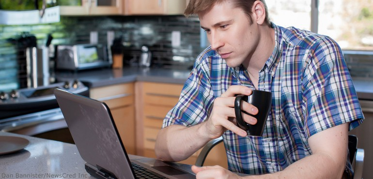 White male sitting in kitchen while working on a laptop computer
