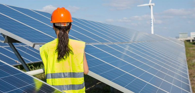 Woman engineer standing next to industrial size solar panels