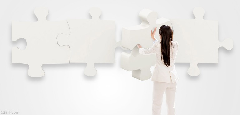 Woman holding a large puzzle piece trying to put it on a wall