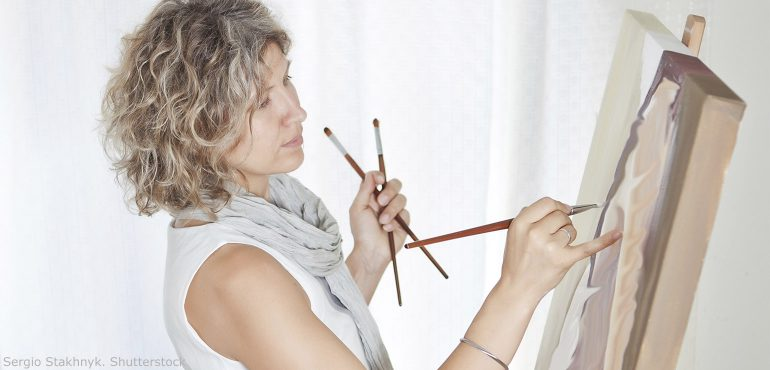 Woman holding paint brushes while painting on a canvas