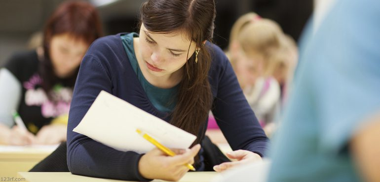 Young adult female student sitting at a classrrom desk looking down at a paper she is holding