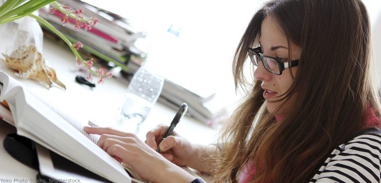 Young adult female student sitting at home desk looking at books and taking notes