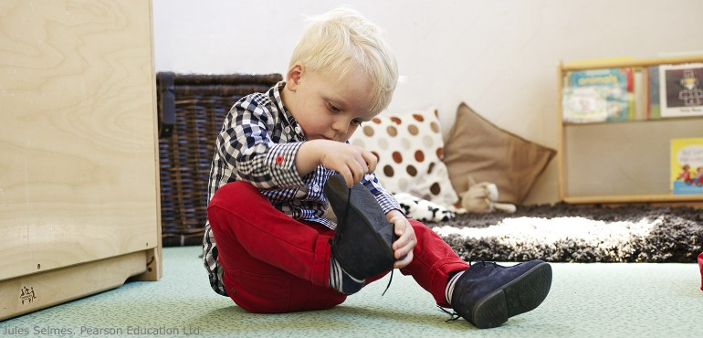 Young boy trying to tie his shoes