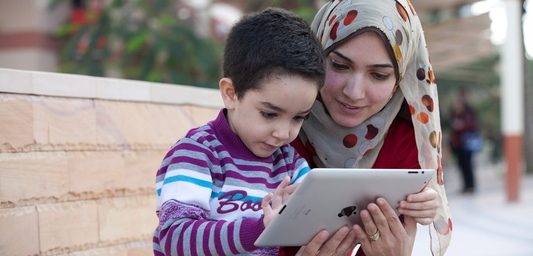 Young boy with mom playing with a tablet