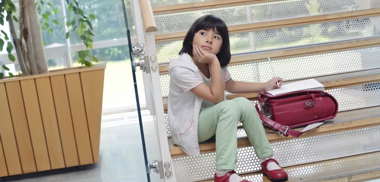 Young girl looking left while sitting on stairs