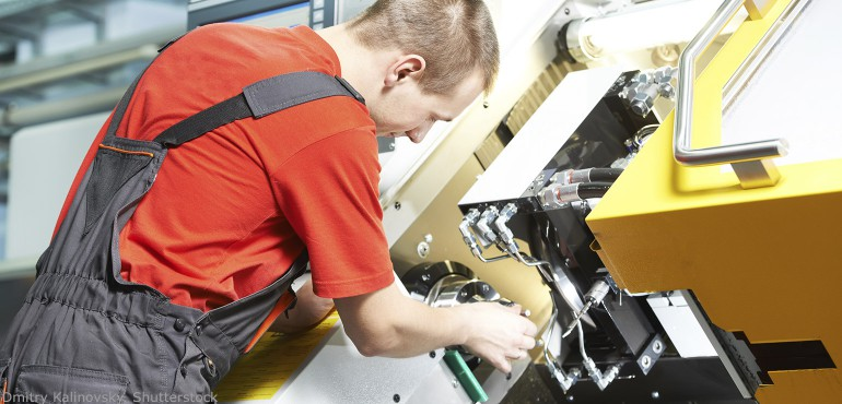 Young man working on an industrial manufacturing machine