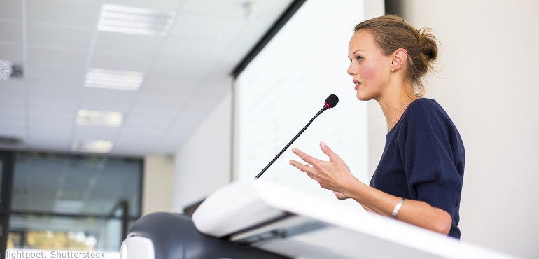 Young woman giving a presentation in a conference side view