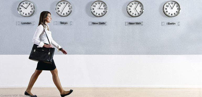 Young woman walking by wall clocks set to different timezones