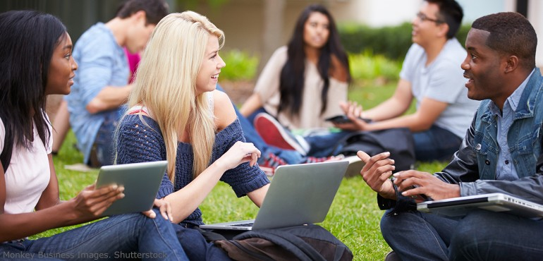 college students talking on a lawn