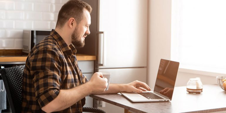 Man in flannel shirt working on laptop with coffee
